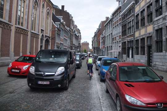 Parked cars and traffic dominate in Liège's city centre.